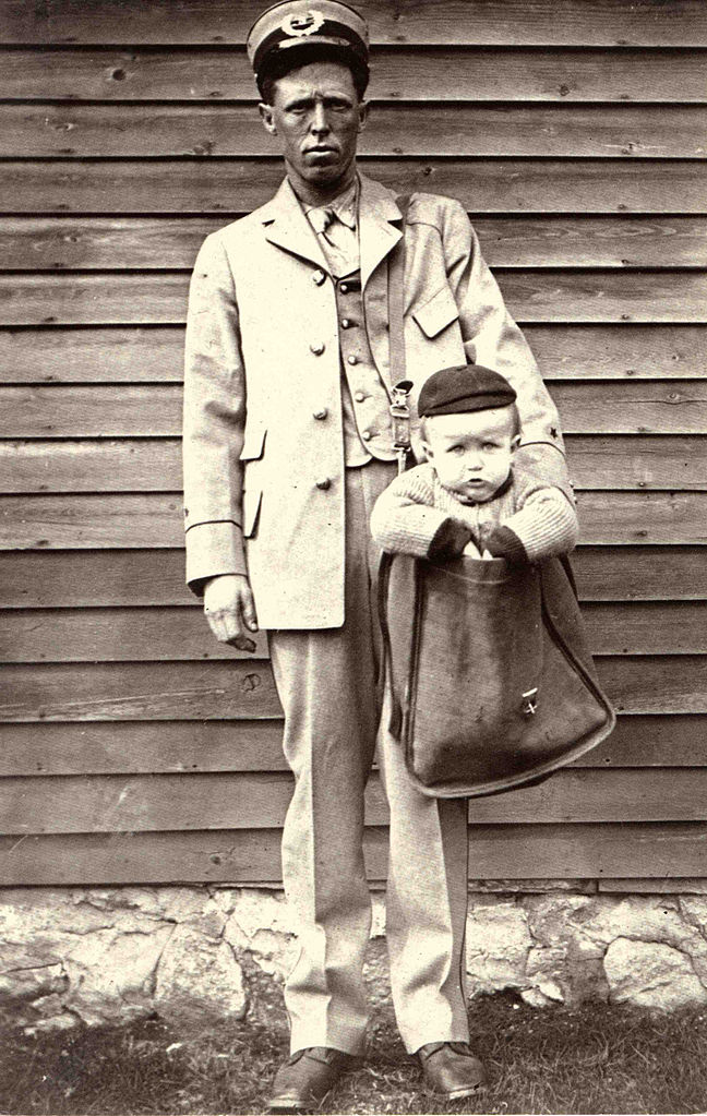 648px-Uniformed_Letter_Carrier_with_Child_in_Mailbag